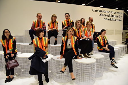 在溫哥華室內設計展IDS上,由Caesarstone設計的前衛大理石板凳,這群媒體人個個歡天喜地坐在上面似乎不願下來。(童宇/大紀元)