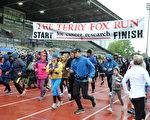 近百名市民從體育場出發,開始本次雨中的本拿比市的泰瑞·福克斯長跑。(童宇/大紀元)