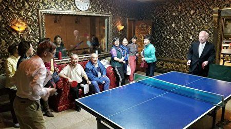 艾维乐与老人们对打乒乓球,切磋球技。