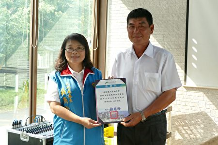 南投县政府民政处长吴燕玲(左)致赠感谢状给协办活动的大鞍狮子会代表。