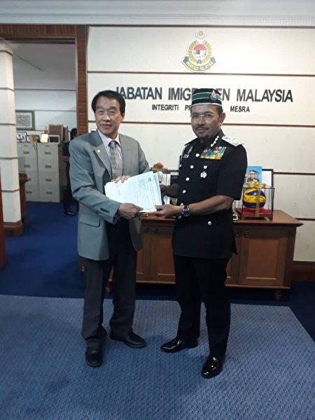 馬來西亞(旅美)聯誼會董事會主席邦君雄(左)向馬來西亞移民局總監(Seri Mustafar Ali,右)遞交反映僑民護照問題的文件。