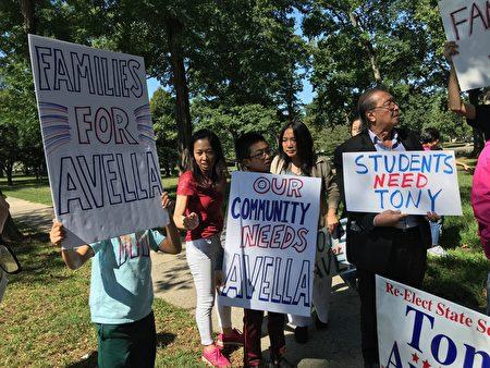 """居民手举""""我们的社区需要艾维乐""""等标语牌。"""