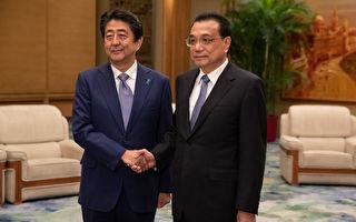 日本首相安倍晉三今天下午抵達北京,展開對中國的正式訪問。圖為安倍晉三(左)與中共國務院總理李克強(右)。(ROMAN PILIPEY/AFP/Getty Images)