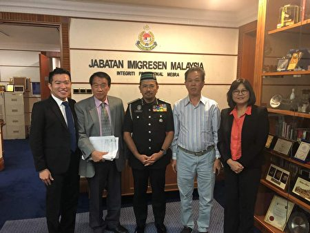 馬來西亞(旅美)聯誼會董事會主席邦君雄(左二)向馬來西亞移民局總監(Seri Mustafar Ali,中)遞交反映僑民護照問題的文件。
