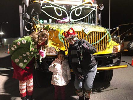 """两位校车花车上的老师身着节日服装,手拿着法轮功学员赠与的中英文""""法轮大法好""""的小莲花和孩子们愉快地合影。"""