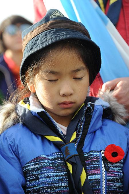 11月11日,本拿比市在南部青年活动中心举行军人纪念日活动,缅怀为国捐躯的加拿大将士。图为默哀的儿童。