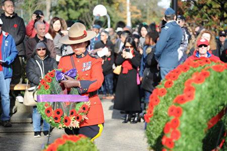 11月11日,本拿比市在南部青年活动中心举行荣军日纪念活动,缅怀为国捐躯的加拿大将士。图为皇家骑警代表敬献花环。