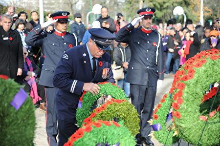 11月11日,本拿比市在南部青年活动中心举行荣军日纪念活动,缅怀为国捐躯的加拿大将士。图为本拿比消防队代表献花环。
