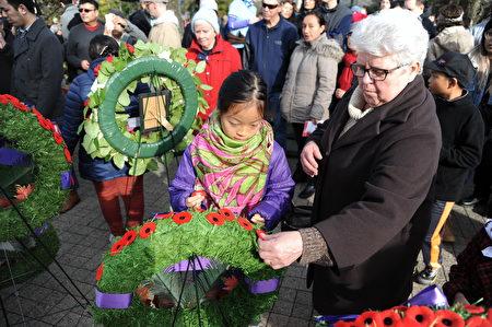 11月11日,本拿比市在南部青年活动中心举行荣军日纪念活动,缅怀为国捐躯的加拿大将士。图为参加纪念活动的市民献上罂粟花。