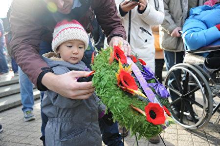 11月11日,本拿比市在南部青年活动中心举行荣军日纪念活动,缅怀为国捐躯的加拿大将士。图为参加纪念活动的儿童献上罂粟花。