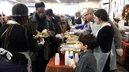 在纽约上西城国家行动网络(National Action Network)总部的大厅中,挤满了前来享用感恩节大餐的民众。