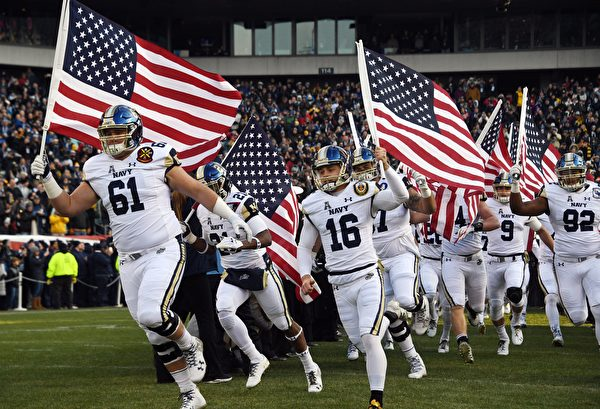 TOPSHOT - Players of the Navy Midshipmen of the US Naval Academy (USNA) arrive waving the American flag prior to the annual Army-Navy football game at Lincoln Financial Field in Philadelphia, Pennsylvania, December 8, 2018. - US President Donald Trump  will officiate the coin toss between the Army Black Knights of the US Military Academy (USMA) and the Navy Midshipmen of the US Naval Academy (USNA). (Photo by Jim WATSON / AFP)        (Photo credit should read JIM WATSON/AFP/Getty Images)