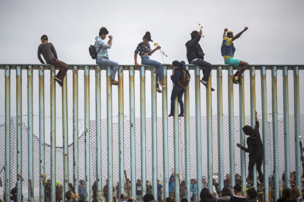 TIJUANA, MEXICO - APRIL 29: People climb a section of border fence to look toward supporters in the U.S. as members of a caravan of Central American asylum seekers arrive to a rally on April 29, 2018 in Tijuana, Baja California Norte, Mexico. More than 300 immigrants, the remnants of a caravan of Central Americans that journeyed across Mexico to ask for asylum in the United States, have reached the border to apply for legal entry. (Photo by David McNew/Getty Images)