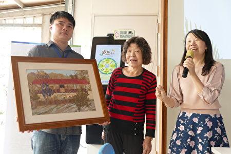 初乡茶间创办人李光曜的妈妈(中)展示押画学习成果。