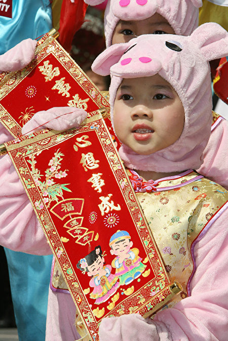 Hong Kong, CHINA: Children dressed in pig costumes take part in a performance at a shopping mall in Hong Kong 30 January 2007. The shopping mall function was held for the upcoming Chinese New Year which falls on 19 February 2007. This year heralds in the Year of the Pig. AFP PHOTO/MIKE CLARKE (Photo credit should read MIKE CLARKE/AFP/Getty Images)