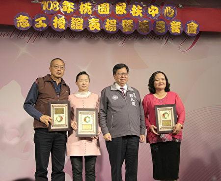 桃园市长郑文灿(左2)与服务满35年的志工合影。
