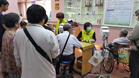 志工協助病人抄寫下血壓數據,方便與醫師溝通