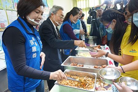 县长张丽善(左一)与总裁王文渊(左二)为小朋友打菜。