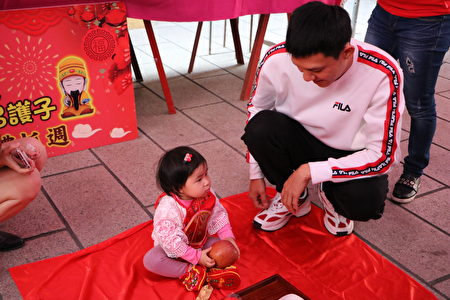 1岁1个月的萧子芸小朋友拿到苹果,代表平平安安。