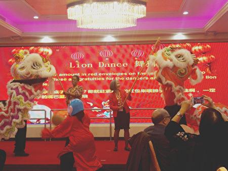 """新年春宴中舞狮""""采青"""",有""""生财""""之意涵。"""