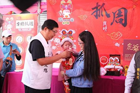 市议员蔡文旭为小朋友戴上金锁片。
