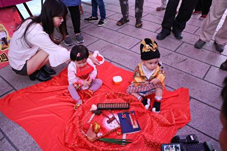 """身穿黄帝龙袍的唐齐小朋友(1岁1个月)成为全场焦点,一手抓起象征""""学者、教师""""的毛笔。"""