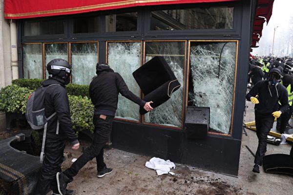 图为身穿黑衣、带黑帽子或头盔且蒙面的破坏者们(casseurs)正在砸毁Le Fouquet's餐厅的玻璃窗。(ZAKARIA ABDELKAFI/AFP/Getty Images)
