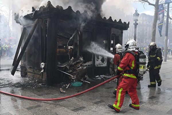 3月16日,巴黎香街上被黄背心示威者烧毁的法国传统式售报亭。图为消费员正在灭火(ALAIN JOCARD/AFP/Getty Images)