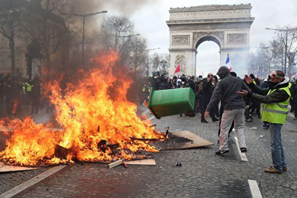 3月16日,黄背心示威者在戴高乐广场上放置燃烧物,凯旋门前浓烟滚滚。(ZAKARIA ABDELKAFI/AFP/Getty Images)
