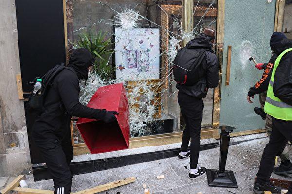 3月16日,在第18轮黄背心示威活动中,身穿黑衣的破坏者(casseurs)正在砸毁商店的玻璃窗。(ZAKARIA ABDELKAFI/AFP/Getty Images)