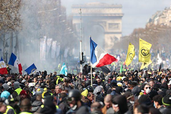 3月16日,黄背心示威者集结在巴黎香榭丽舍大道上,有些人穿着黄色背心,但许多身穿黑衣、带黑帽子或头盔且蒙面的人也与抗议者混在一起。(ZAKARIA ABDELKAFI/AFP/Getty Images)