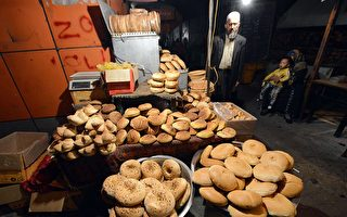 曾經烏魯木齊街頭的新鮮烤饢的小吃攤已不復存在。饢對維吾爾族人就像法式長棍麵包之於法國人一樣或不可缺。(GOH CHAI HIN/AFP/Getty Images)