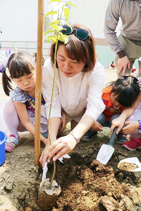 市长黄敏惠与幸福幼儿园小朋友一起植树。