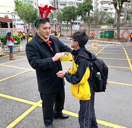 大成国中校长苏佐玺(左)圣诞节于校门口,发糖果给上学的学生,温馨满校园。