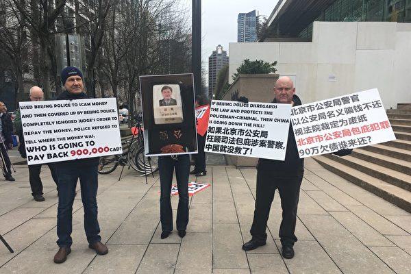孟晚舟在溫哥華出庭當天,庭外一位溫哥華華裔女子和同伴,舉牌控告北京警察詐騙90加元。(余天白/大紀元)