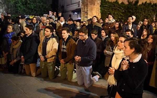 4月15日,法国巴黎圣母院突发大火,许多人伤心地跪下祈祷。(ERIC FEFERBERG/AFP/Getty Images)