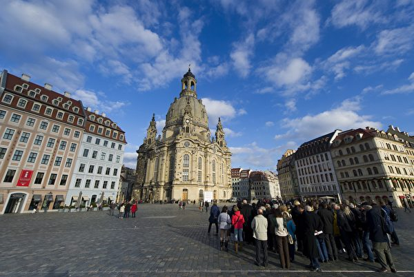 Tourists look at the Frauenkirche ( Church of Our Lady ) in Dresden, eastern Germany, on November 16, 2015. The church is an identical version of the original Frauenkirche, built with what was salvaged from the remains of the former church after allied bombing at the end of WWII. AFP PHOTO / ROBERT MICHAEL (Photo credit should read ROBERT MICHAEL/AFP/Getty Images)