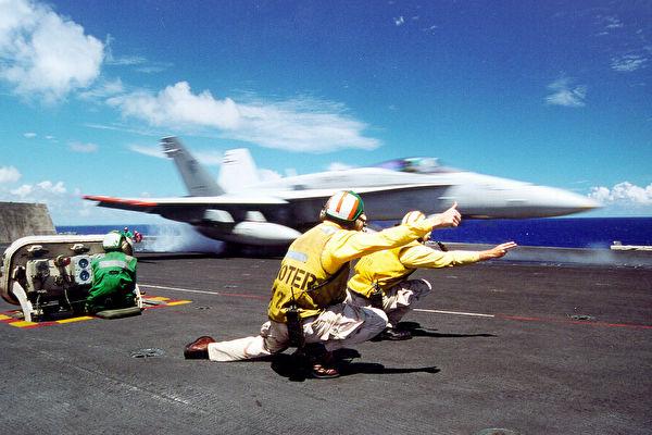 2001年9月27日,甲板指導員指導F/A-18大黃蜂式戰鬥攻擊機從肯尼迪號航空母艦起飛資料照。 (U.S. Navy/Getty Images)