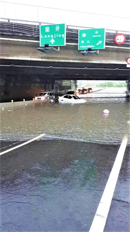 五权西路交流道下方积水,多部车辆困水中、载浮载沉。