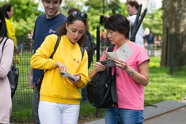 5月18日,來自全世界的部分法輪功學員在紐約曼哈頓的砲台公園煉功,學員也為民眾講述法輪功的真相。(張靜怡/大紀元)