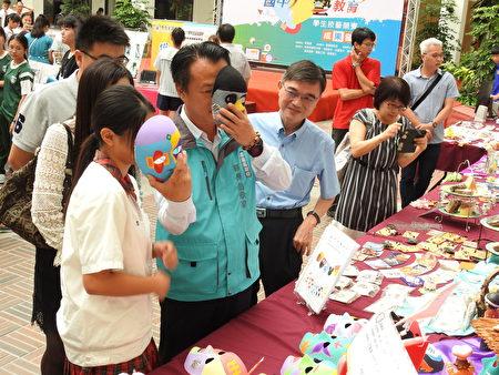 嘉義縣長翁章梁(如圖)是義竹國中校友,在義竹國中攤位和小學妹一同戴上彩繪臉譜面具,體驗其樂趣。