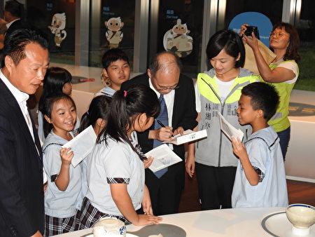 在故宫南院儿童创意中心所举行的记者会中,小朋友争相排队请故宫院长吴密察(执笔签名者)签名留念。