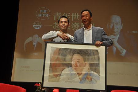 有意參選總統的鴻海科技集團總裁郭台銘(右)17日到花蓮東華大學進行座談,有學生(左)特地送上一幅熬夜畫出郭台銘年輕時的肖像,讓郭董大為感動。