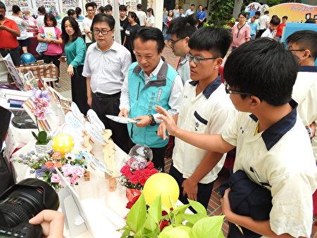 嘉義縣長翁章梁(右3)在成果發表會中,用心聽布袋國中學生解說創意造型扇子、氣球,熱昇華馬克杯的製作要領。