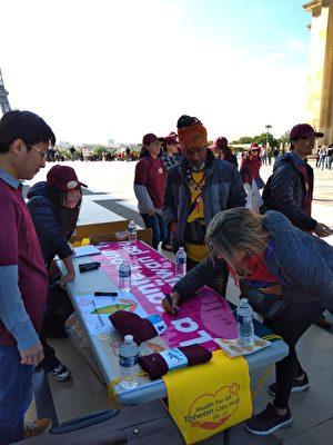 民眾簽名聯署支持台灣參與世界衛生組織。(駐法國臺北代表處提供)
