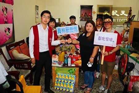 彰化家扶员展志工队队长张维哲(左一)亲手将粽子送给扶助家庭。