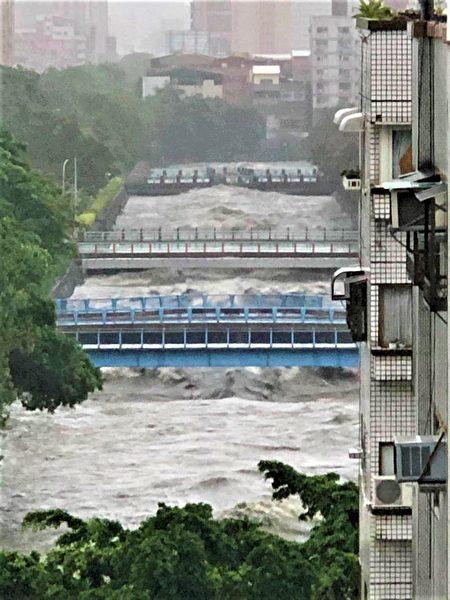 从高处拍下,台中市区麻园头溪因暴雨,水面暴涨、淹过桥面的惊险画面。