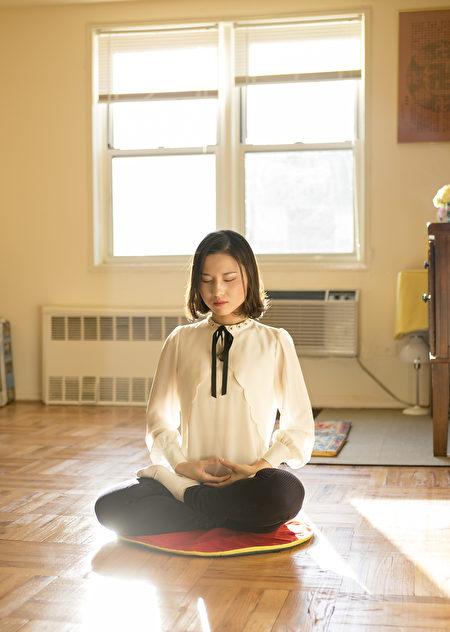 李扶搖在紐約皇后區的家中展示法輪功打坐。她和父母於2014年逃離中國,最終獲得庇護。(Samira Bouaou/Epoch Times)