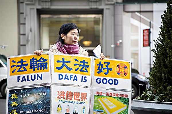 王会娟在纽约曼哈顿帝国大厦前举展板,帮助中国游客了解中共迫害法轮功的真相。(Samira Bouaou/Epoch Times)