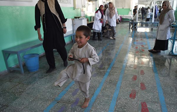 Ahmad Sayed Rahman, a five-year-old Afghan boy who lost his right leg when he was hit by a bullet in the crossfire of a battle, walks without his prosthetic leg at the International Committee of the Red Cross (ICRC) hospital for war victims and the disabled, in Kabul on May 7, 2019. - With his hands in the air and an infectious grin spreading from ear to ear, a young Afghan boy whirls around a Kabul hospital room on his new prosthetic leg. The boy, five-year-old Ahmad Sayed Rahman, has become a social media star in Afghanistan and beyond after a short video of him effortlessly dancing on his new limb was published this week on Twitter. (Photo by WAKIL KOHSAR / AFP) (Photo credit should read WAKIL KOHSAR/AFP/Getty Images)